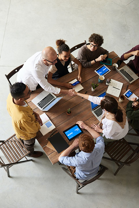 People sitting around a table with laptops