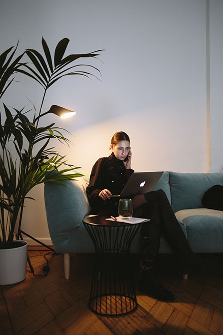 Woman working on laptop while sitting on couch