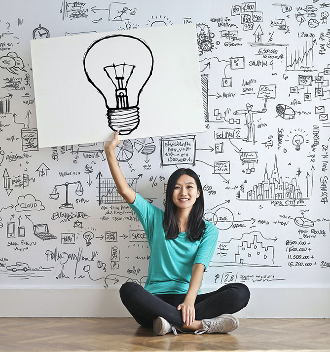 lady holding poster with light bulb drawing