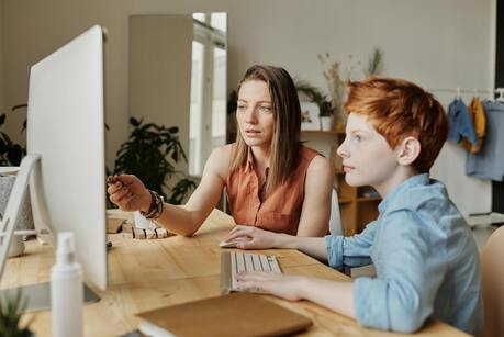 A young boy being homeschooled by his mother, both looking at a computer.