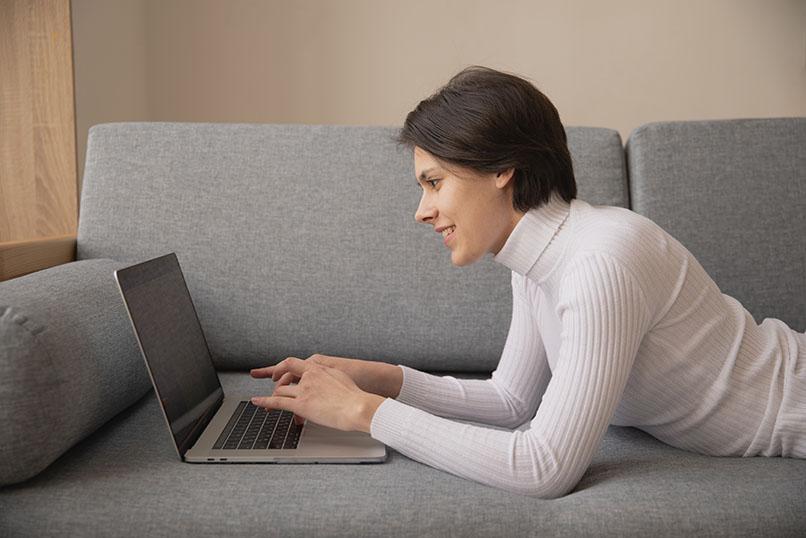 Lady working on laptop on sofa