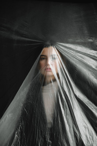 A sombre looking brunette woman behind a plastic sheet, against a black background