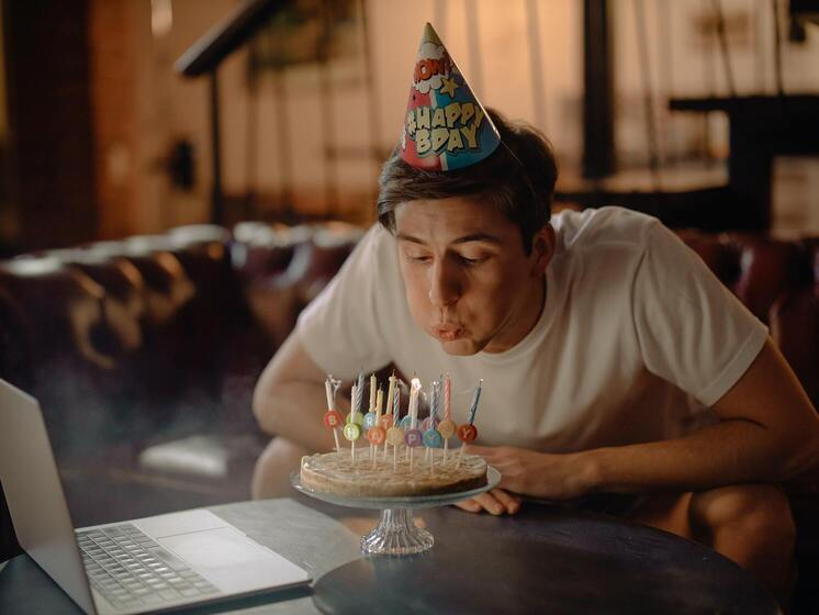 A man blowing out birthday cake candles, alone, with an open laptop in front of him