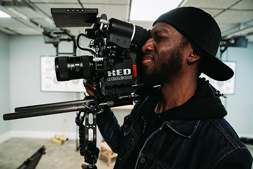 Videographer with video camera on shoulder. hire a freelance videographer, what do freelance videographers charge, freelance videographer day rate, freelance video producer rates, freelance videographer rates, freelance video production rates, how much do videographers make